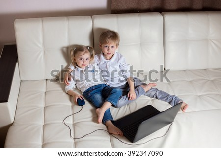 two happy young children: white-skinned blond boy girl sitting in an embrace (brother and sister) on a white sofa watching cartoons on a laptop - stock photo