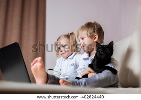 two happy young children: white-skinned boy blond girl sitting with a black cat and noutbukomego (brother and sister) on a white sofa watching cartoons with your computer - stock photo