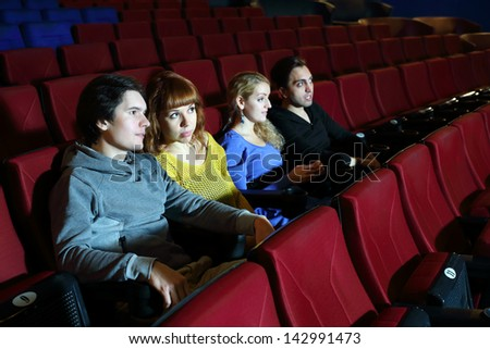 Two happy young couples look movie and talk in cinema theater. Focus on left pair.
