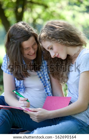 Two happy young female college students working together as they sit outdoors in the garden poring over a shared file
