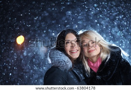 Two happy young female friends enjoying snowfall on Christmas winter night over snow background. Copyspace.