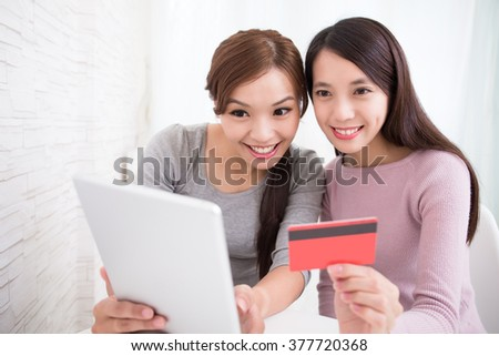 Two happy young female friends  shopping on internet by digital tablet pc, asian beauty