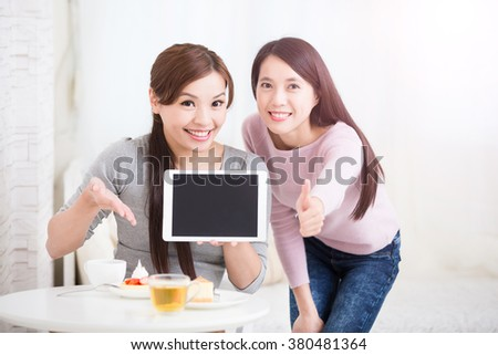 Two happy young female friends show empty digital tablet pc and show thumb up, great for your design, asian beauty