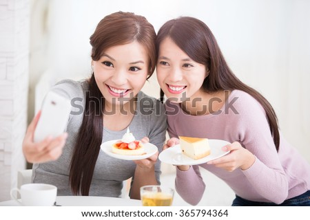 Two happy young female friends take selfie picture by smart phone, with coffee cups and cakes in the living room at home, healthy lifestyle concept, asian beauty - stock photo