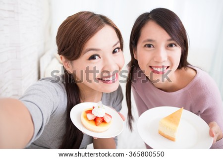 Two happy young female friends take selfie picture with coffee cups and cakes in the living room at home, asian beauty - stock photo