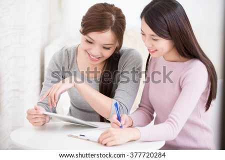 Two happy young female friends use digital tablet pc and write something, asian beauty