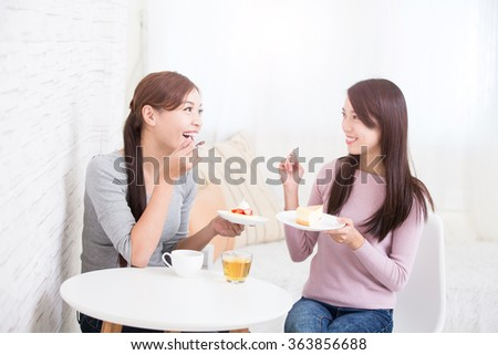 Two happy young female friends with coffee cups and cakes enjoying a conversation in the living room at home, healthy lifestyle concept, asian beauty - stock photo