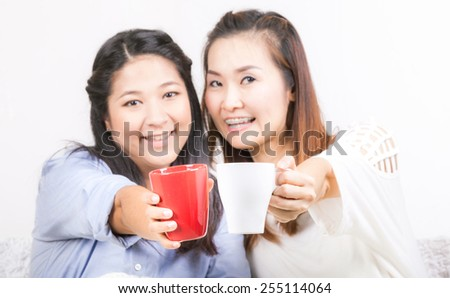 Two happy young female friends with coffee cups enjoying a conversation - stock photo
