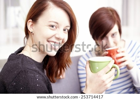 Two happy young female friends with coffee cups enjoying a conversation in the living room at home