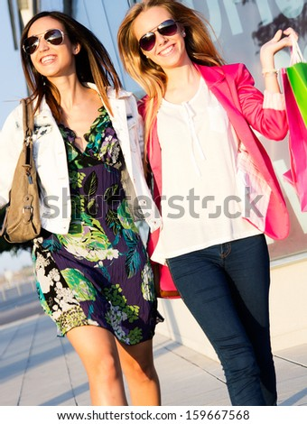 two happy young friends shopping together in town - stock photo