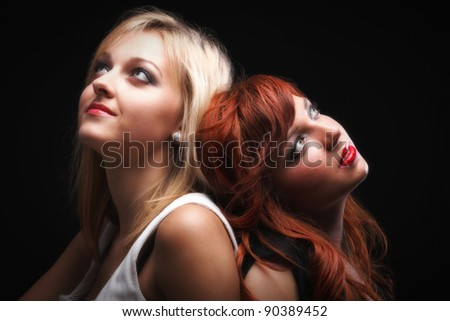 two happy young girlfriends blonde and red-hair black background Glamour - stock photo