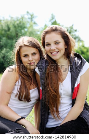 Two happy young girlfriends on the nature - stock photo