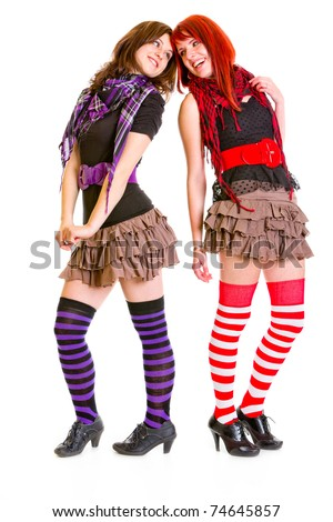 Two happy  young girlfriends standing back to back and looking at each other isolated on white - stock photo