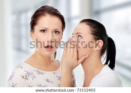 Two happy young girlfriends talking - stock photo