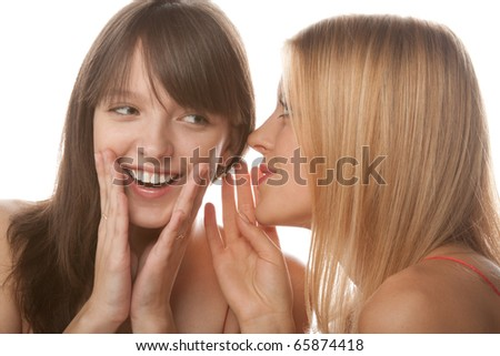 two happy young girlfriends talking over white gossip
