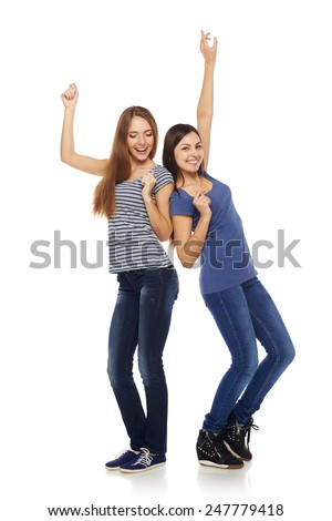 Two happy young girls friends dancing of joy in full length, isolated on white background - stock photo