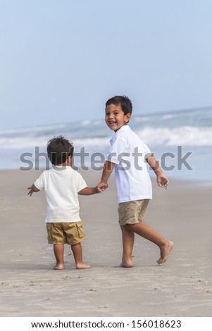 Two happy young hispanic boy children brothers playing together on a beach