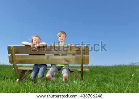Two happy young kids sitting on a bench in summer - stock photo
