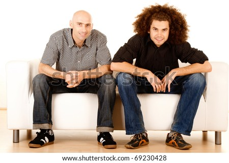 Two happy young male friends relaxing on sofa or settee, white background.