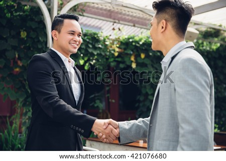 Two happy young men shaking hands in the rest area of the office - stock photo