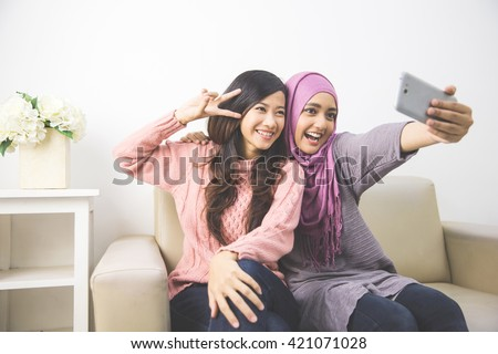 two happy young muslim woman take self portrait with handphone at home