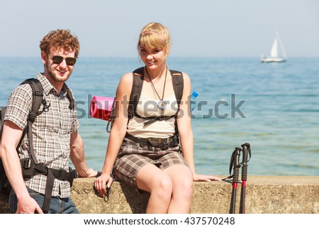 Two happy young people tourists hiking by sea ocean water. Backpackers couple on summer vacation trip journey.