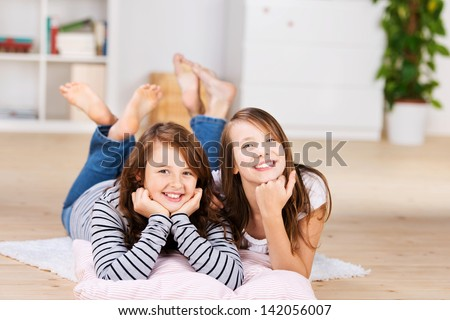 Two happy young teenage girls smiling to camera while laying on the bedroom floor over pillows