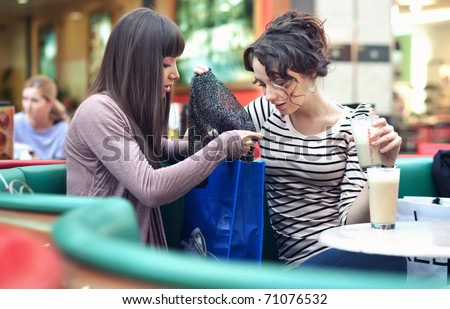 Two happy young woman choose clothes in shop holding shopping bag
