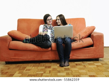 two happy young woman working on laptop computer on red sofa isolated on white