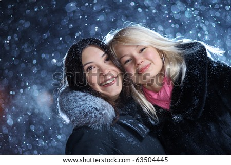 Two happy young women enjoying snow, closeup.