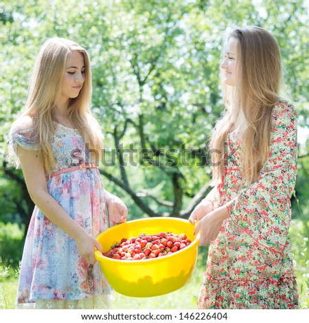 Two happy young women gathering strawberry on bright summer day - stock photo