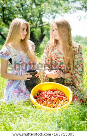Two happy young women gathering strawberry on bright summer day outdoors background