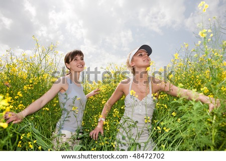 Two happy young women in a field
