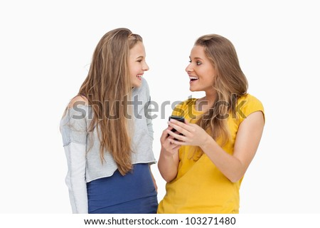 Two happy young women looking a smartphone against white background
