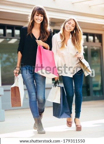 Two happy young women shopping at the mall - stock photo