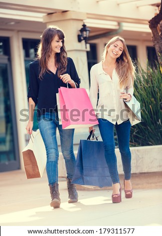 Two happy young women shopping at the mall