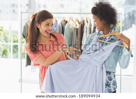 Two happy young women shopping in clothes store - stock photo