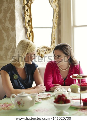 Two happy young women sitting at dining table - stock photo