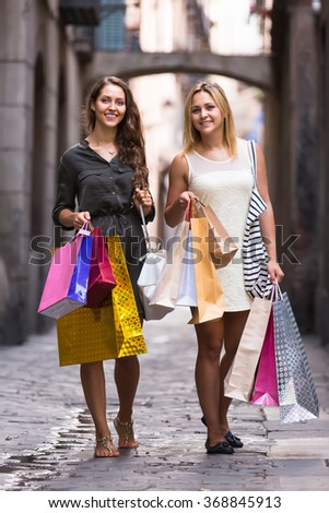 Two happy young women walking by street with shopping bags