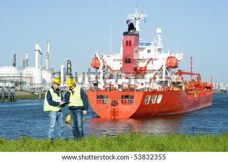 Two harbor workers at a petrochemical refinery harbor hard hats and safety vests discussing docking schedules - stock photo