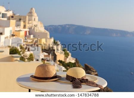 two hats on Santorini island image of honeymoon and summer vacation - stock photo