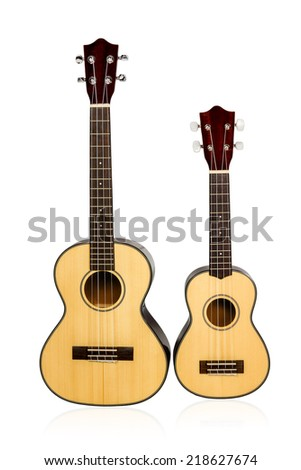 Two Hawaiian ukulele standing next to each other in different sizes light brown front view isolated on white background - stock photo
