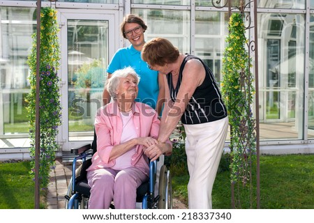 Two Health Care Professionals for Old Age Patient on Wheel Chair. Captured at Home Care Garden. - stock photo