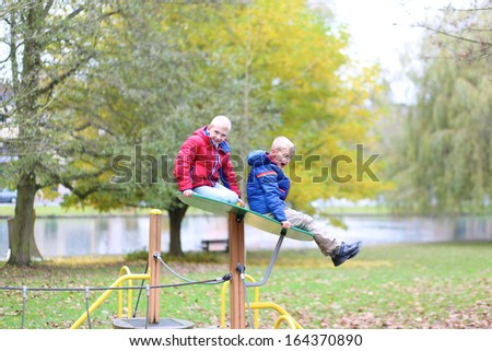 Two healthy boys, twin brothers in colorful warm coats having fun on the playground in the park on a sunny autumn day - stock photo