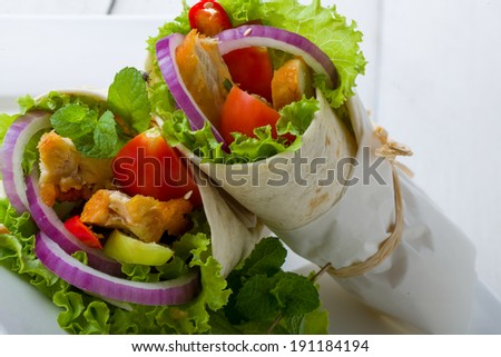 Two healthy chicken tortillas with fresh salad ingredients icluding lettuce, onion and tomato wrapped in white paper for a delcious takeaway - stock photo