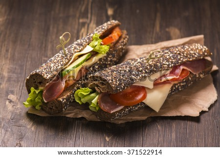 Two healthy sandwiches with ham, cheese and vegetables over grunge wooden background. Toned image. Selective focus - stock photo
