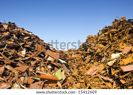 two heaps of different kinds of metal scrap in a scrap yard - stock photo