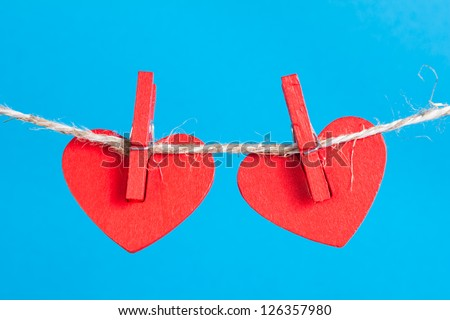 Two heart on clothesline with clothespins, blue background - stock photo