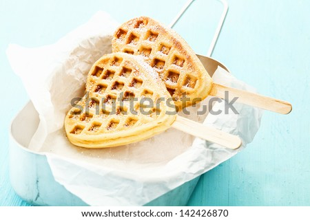 Two heart shaped Belgian waffles on a stick inside a tin can a a paper wrap, sprinkled with cinnamon and sugar - stock photo