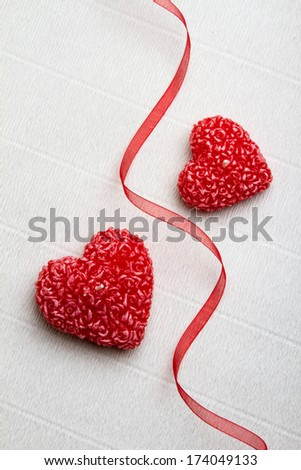 Two heart-shaped candles separated by a red ribbon. Valentine da